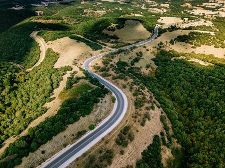 Luchtfoto boven weergave van een landelijk landschap met een bochtige weg die het doorneemt in Griekenland. Drone fotografie Stockfoto