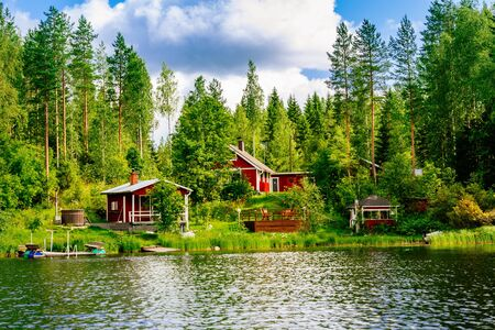 A traditional Finnish wooden cottage with a sauna and a barn on the lake shore. Summer landscape. Rural Finland.