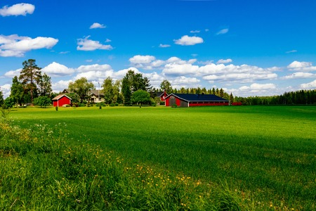 Traditional red farm house barn with white trim in open pasture with blue sky in rural Finland