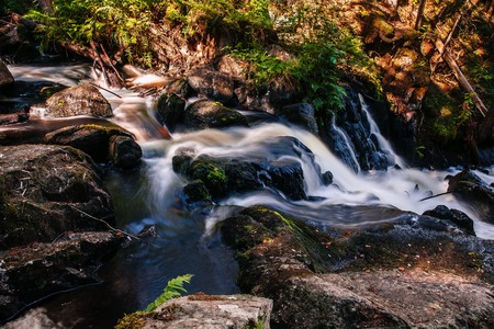 Fast river flowing stream water of waterfall in Finland