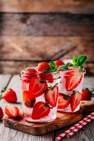 Infused detox water with  strawberry and mint. Ice cold summer cocktail or lemonade in glass mason jar