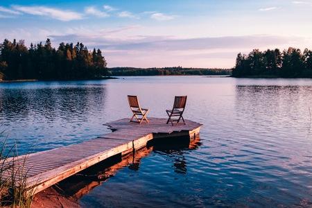 Twee houten stoelen op een houten pier met uitzicht op een meer bij zonsondergang in Finland