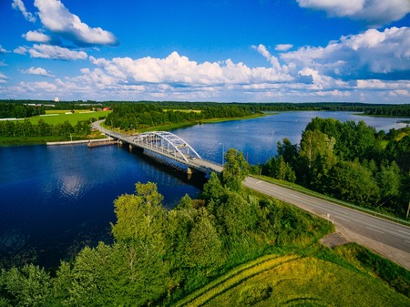 Aerial view on bridge over blue lake in summer day in rural Finland countryside with green and yellow fields