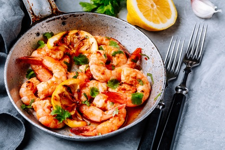 Spicy garlic chilli Prawns Shrimps on frying pan with lemon and cilantro Stock Photo