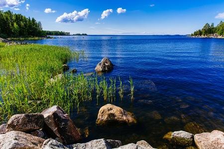 Helder water blauw meer met stenen en groen bos op een zonnige zomerdag op het platteland van Finland. Stockfoto