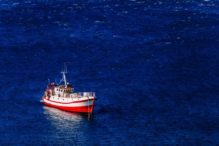 Aerial view of red fishing boat on a deep blue sea in harbor. Greece.