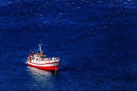 Luchtfoto van rode vissersboot op een diepblauwe zee in de haven. Griekenland.