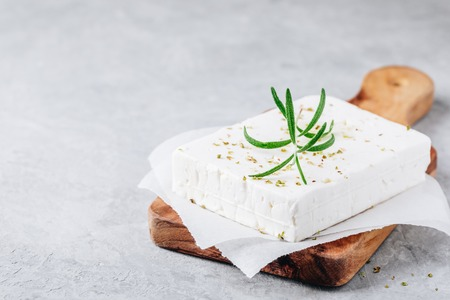 Homemade greek cheese feta with rosemary and herbs on wooden cutting board