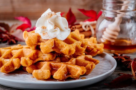 Pumpkin spice waffles with whipped cream on wooden background for Thanksgiving Day. Stock Photo