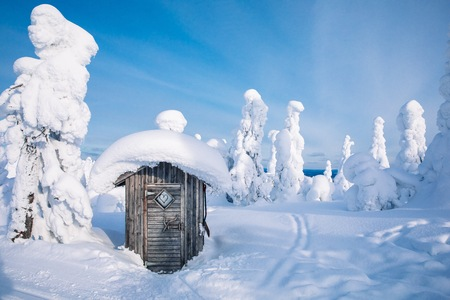 Old rustic wooden hut in winter snowy forest in Finland, Lapland. Stock Photo