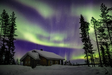 Piękna fioletowa i zielona zorza polarna (Aurora Borealis) na nocnym niebie nad zimowym krajobrazem Laponii, Finlandii, Skandynawii