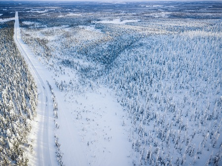 Aerial view of snow covered winter forest and road. Beautiful rural landscape in Finland, Lapland. Banco de Imagens