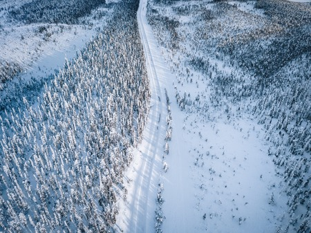Aerial view of snow covered winter forest and road. Beautiful rural landscape in Finland, Lapland. Stock Photo