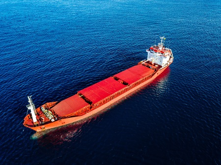 Aerial view of general cargo ship in blue sea in Italy. View from above of red empty container ship in the sea.