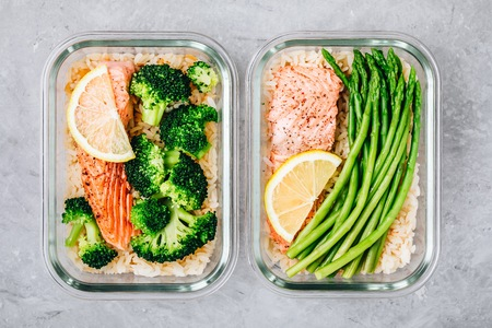 Meal prep lunch box containers with grilled salmon fish, rice, green broccoli and asparagus 写真素材