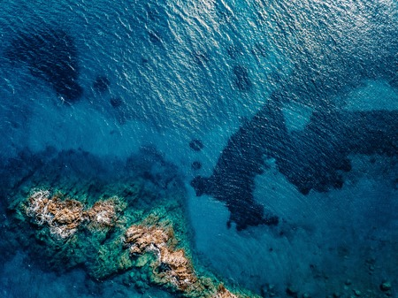 Aerial view of ocean waves and rocks. Blue and turquoise sea surface.