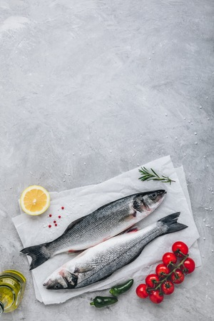 Fresh raw fish sea bass (seabass) with rosemary and vegetables on gray stone background. Top view.