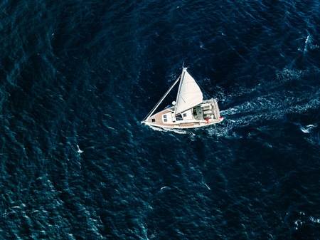 Aerial view of Sailing ship yachts with white sails in windy condition in deep blue sea