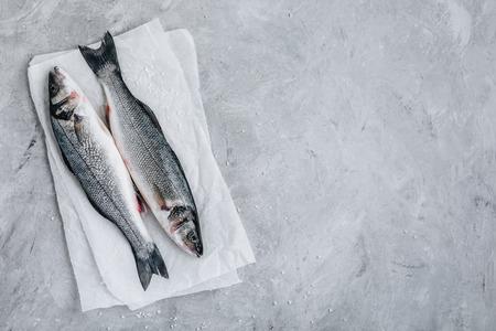 Fresh raw fish sea bass (seabass) with  sea salt on gray stone background. Top view.