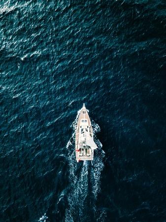 Vue aérienne des yachts de voilier avec des voiles blanches dans des conditions venteuses en mer d'un bleu profond