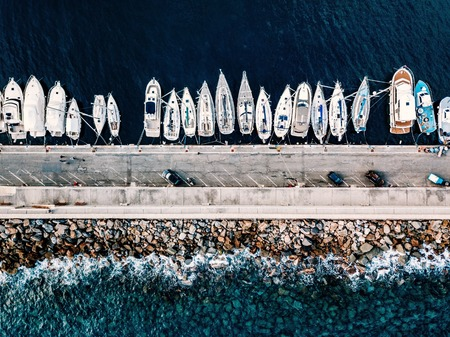 Aerial view of marina with boats and yachts in Italy. Blue sea landscape with white yachts from above