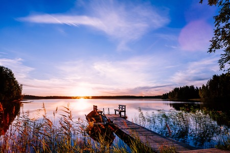 Holzsteg mit Fischerboot bei Sonnenuntergang auf einem See im ländlichen Finnland rural