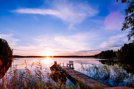 Pilastro di legno con il peschereccio al tramonto su un lago in Finlandia rurale