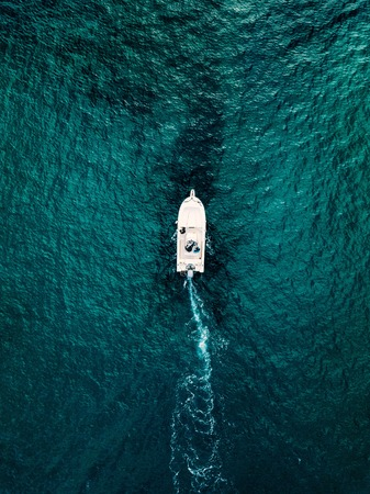 Aerial view of speed boat in motion in blue sea in Italy. Water transportation and summer leisure time activity.