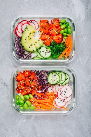 Poke meal prep containers with salmon, rice, radish, cucumber and avocado. Top view, copy space
