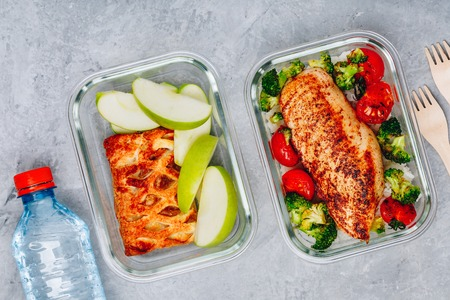Grilled chicken meal prep containers with rice, broccoli and tomatoes and dessert pie with green apple. Top view