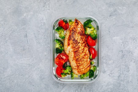 Grilled chicken meal prep containers with rice, broccoli and tomatoes. Healthy lunch with vegetables, copy space