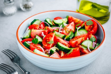 Fresh green summer salad bowl with tomatoes, cucumbers, red onions, basil and olive oil dressing. Zdjęcie Seryjne
