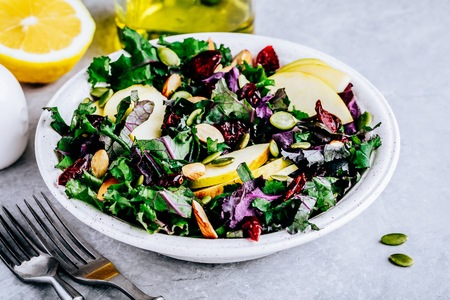 Apple Cranberry Kale Salad bowl with dry cranberries, almonds and pumpkin seeds. Fresh green vegan summer salad