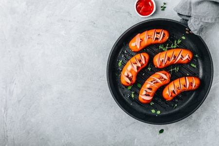 Grilled sausages in cast iron pan. Top view