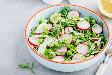 Fresh summer fennel salad with pea shoots and radishes in the bowl