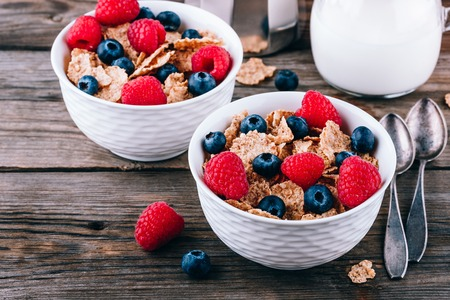 Whole Grain healthy cereals with fresh blueberries and raspberries for breakfast.