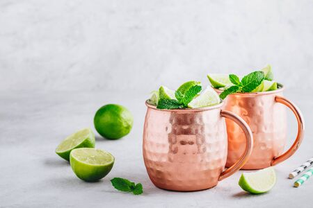 Moscow mule ice cold cocktail in copper cup with lime and and mint on gray stone background, copy space. Stock Photo