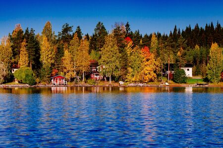 Autumn foliage, fall colorful forest over blue lake with red wooden cabins in Finland.
