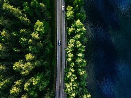 Aerial landscape view of coastline road between green pine forest and blue lake in Finland