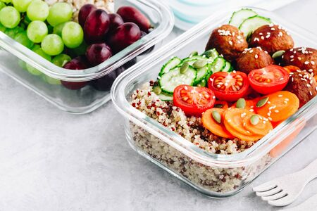 Meal prep lunch box containers with quinoa, meatballs cucumbers, carrots, sesame and pumpkin seeds