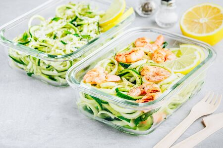 Meal prep lunch box containers Spiralized zucchini noodles pasta with shrimps on gray stone background