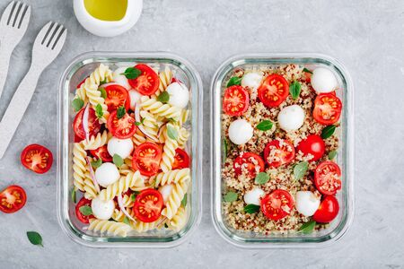 Meal prep containers with pasta salad or quinoa, tomatoes, mozzarella cheese, and basil. Top view, copy space