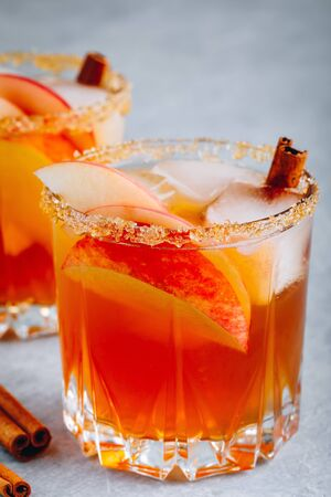 Apple cider margarita with cinnamon and ice for Halloween or Thanksgiving in glass on gray stone background