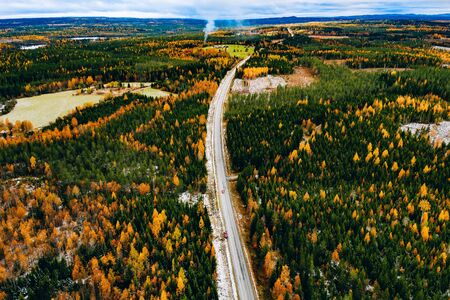 view of first snow autumn color forest and a road with car in Finland Lapland. Banco de Imagens