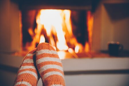 Feet in wool striped socks by the fireplace. Relaxing at a fireplace on winter holiday evening. Foto de archivo