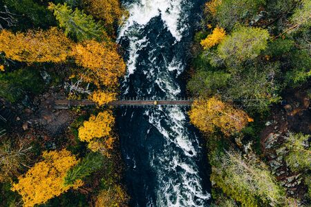 Aerial view of river with suspension bridge in colorful autumn forest in Finland Lapland.
