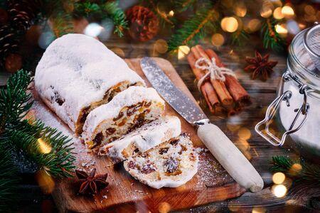 Traditioneller Christstollen-Fruchtkuchen auf rustikalem Holzhintergrund mit Weihnachtsbeleuchtung