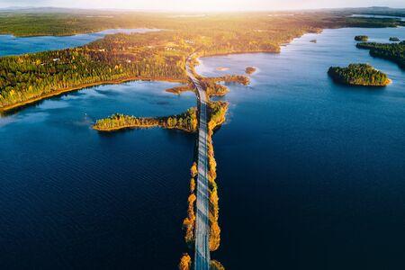 Luftaufnahme der Brücke über blaue Seen mit Sonnenlicht im bunten Herbstwald in Finnland Lappland. Standard-Bild