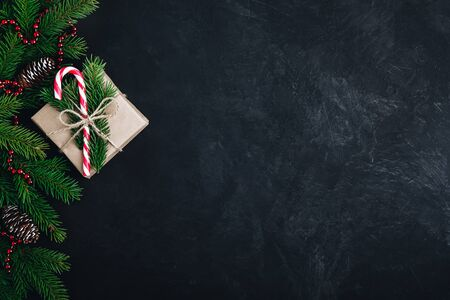 Christmas festive background with christmas tree branches, fir cones and gift box with candy cane on dark concrete stone background. Top view, copy space