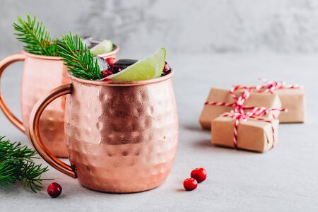 Holiday Moscow Mule ice cold Cocktail in copper cup with cranberries, lime and rosemary on gray stone background.